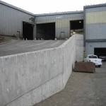 Industrial building and new concrete retaining wall supporting a track ramp to the second floor