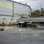 Industrial truck wash featuring a safety rack to support lifted truck bodies